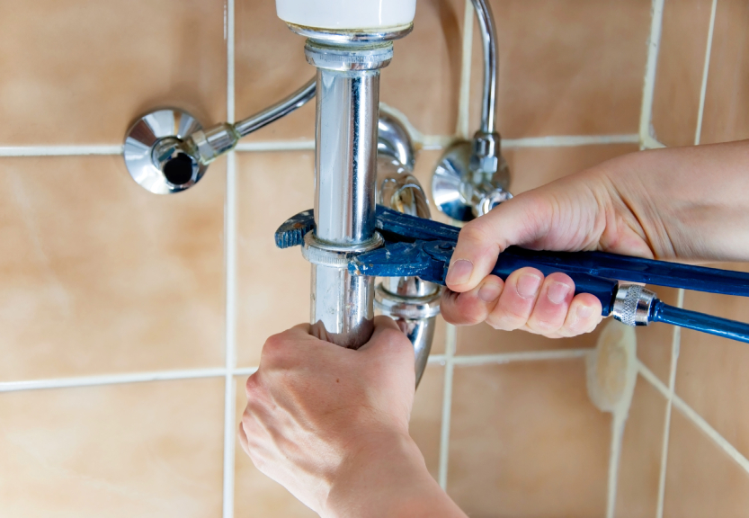 hands of a plumber with sink and wrench